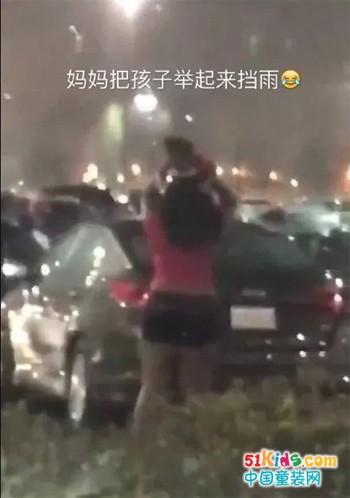 妈妈把孩子举起来挡雨:孩子!雨太大了,妈妈当你是一把伞
